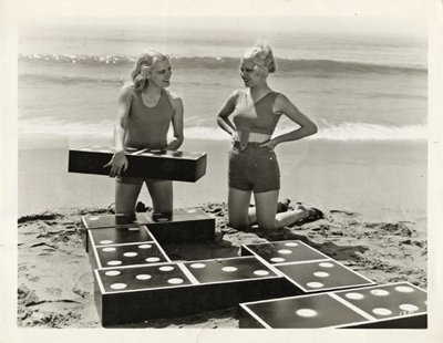 A 1932 photo featuring two hollywood actresses, Joan Marsh and Mary Carlisle playing a game of beach dominoes.