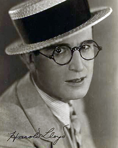 A small 5x7 staged portrait of Harold Lloyd wearing his trademark straw hat and glasses - photograph taken in 1921.