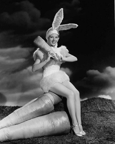 A 1940's publicity portrait by Eugene Robert Richee of a starlet in a bunny outfit sitting on giant carrots.