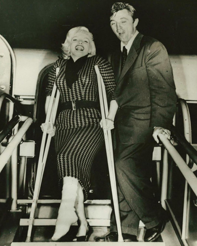 Marilyn Monroe and Robert Mitchum in a candid shot of them leaving a plane after filming River of No Return. Monroe nearly broker her leg on set and is seen in this photograph on crutches with her leg bandaged.
