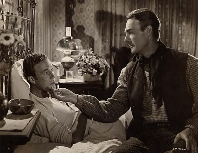 A still from the set of Badman's Territory featuring Randolph Scott and a bedridden James Warren, 1946.