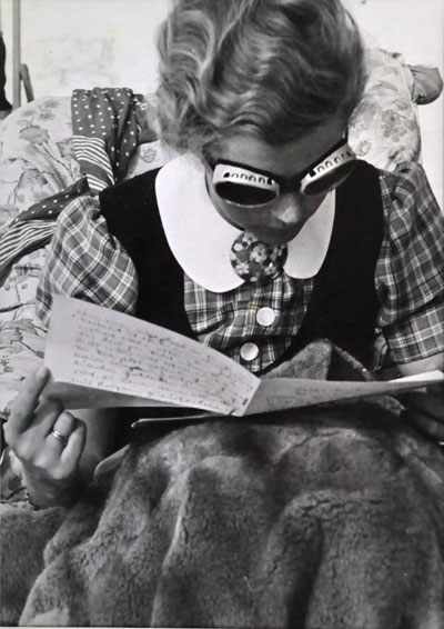 A woman reads in snow goggles, circa 1930.