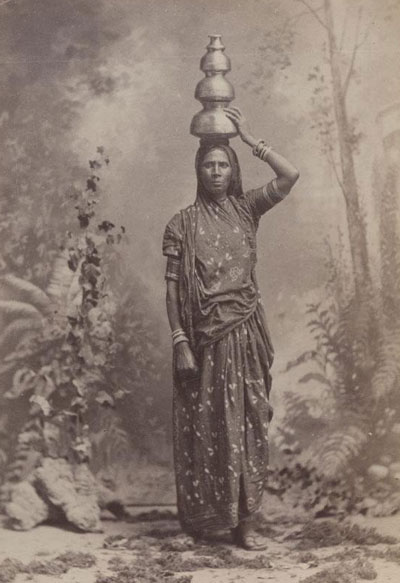 Circa 1880, an Indian woman poses with a jug.