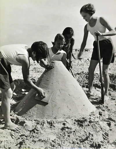Young women build a sandcastle in 1930.