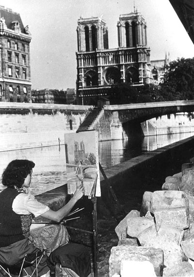 A Parisian woman paints Notre Dame in 1940.