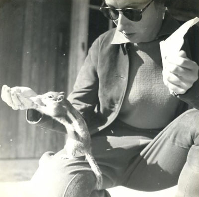 A woman feeds a chipmunk.