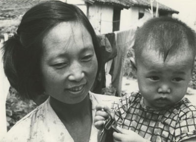 Circa 1964, a Chinese farm woman holds her child.