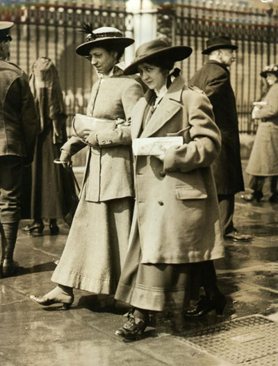 In 1916, a British woman keeps warm in an officer's coat.